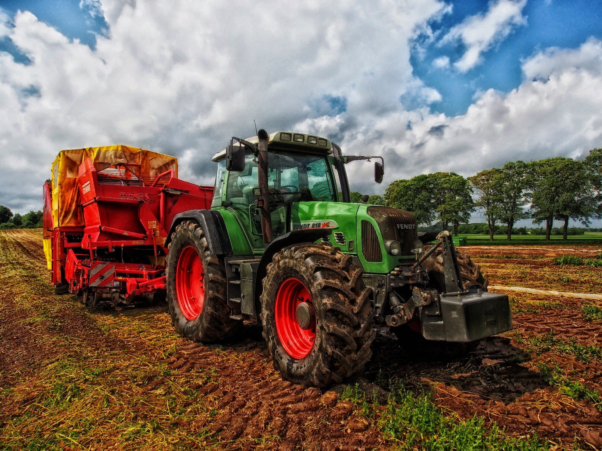 A tractor pulls farm equipment through a field beneath a partly cloudy blue sky. (Pixabay / tpsdave, public domain)